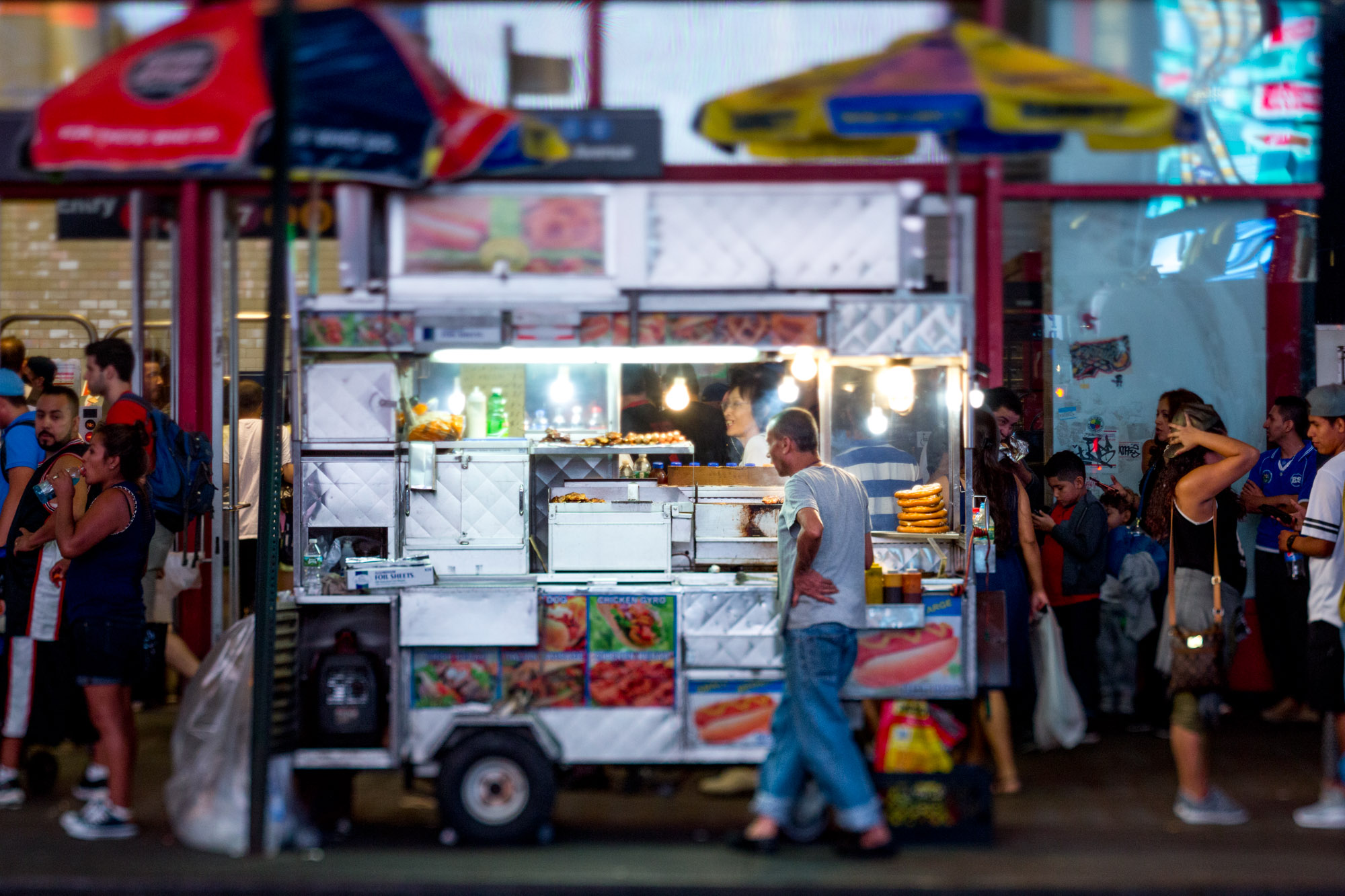 A hardworking man looks tired behind a food cart